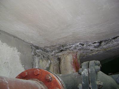 Металлическая труба уходит в бетон - вода бежит в стыке